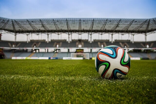 Soccer ball on pitch with empty stands