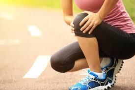 Athlete holding kneed on track, painful